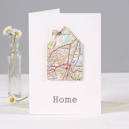 House silhouette cut from vintage map mounted on white card with 'home' printed below.