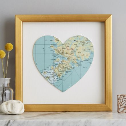 Map location heart in gold frame on marble mantelpiece.