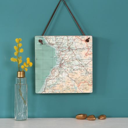 Square wooden block strung with leather cord and hung above shelf featuring map location of your choice.