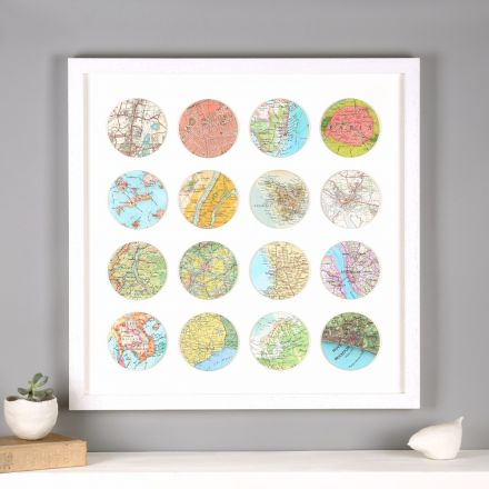 Sixteen map location circles mounted in white wood frame above white mantelpiece.