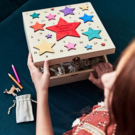 Handmade wooden advent box with coloured stars on lid and numbers 1 to 25.
