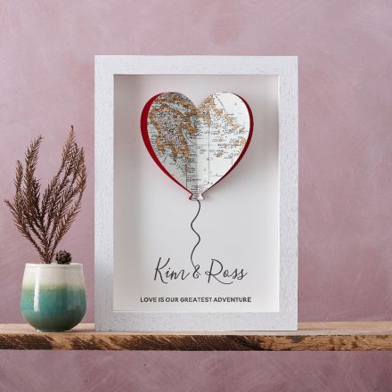 Framed artwork of a balloon silhouette cut from map with a couples names printed beneath and 'Love is our greatest adventure' printed below that. White wood box frame.