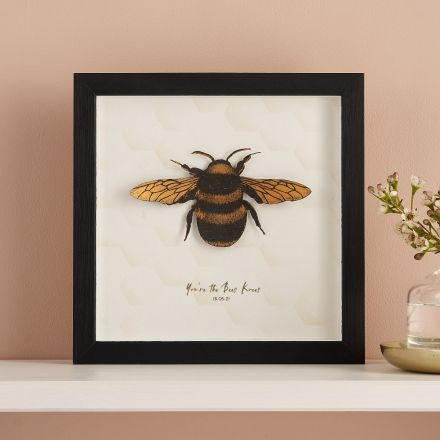 3D paper cut honey bee mounted on white card and framed in black box frame.