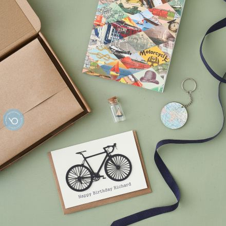 Letterbox gift, personalised bike card, world keyring, boat in a miniature bottle, notebook.