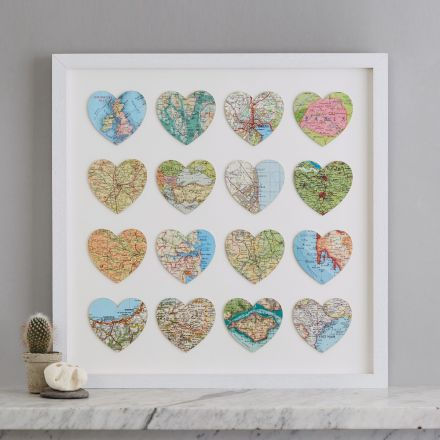 Sixteen personalised map location hearts in white box frame on marble mantelpiece