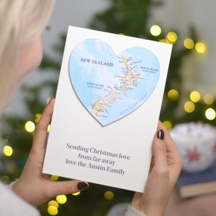 Pesonalised map heart card with personalised message printed underneath. White card with New Zealand map. Held in hands in front of Christmas lights.