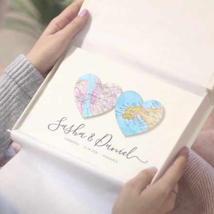 Custom map card showing two map hearts and 'Olivia and Aiden' printed on the front. Held in pale pink gift box.