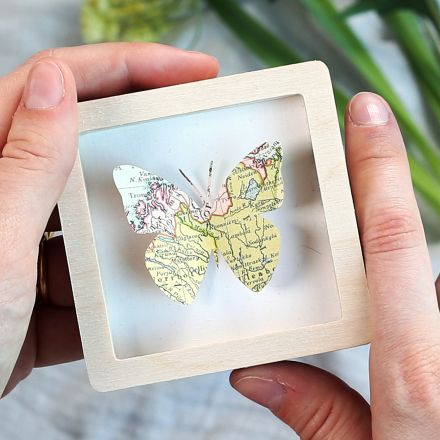Miniature wood frame holding map butterfly.
