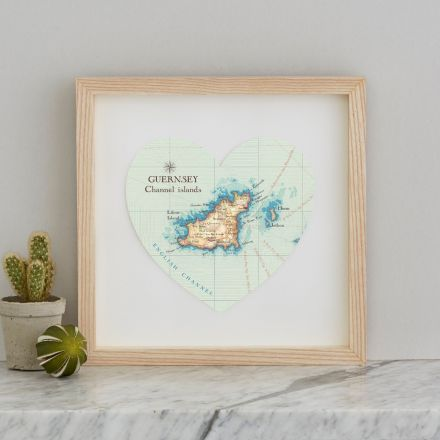 Guernsey Channel Islands map heart mounted on white card and framed in light wood box frame.