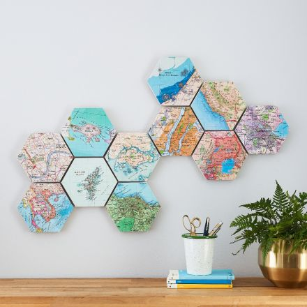 Ten map hexagons mounted on wall above mantelpiece.