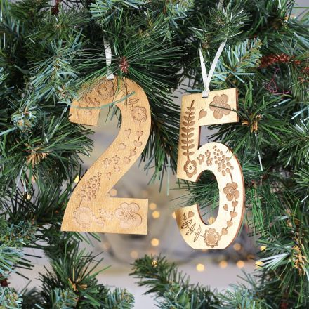 Wooden numbers, engraved with decorative floral design and painted in gold. Strung on cream ribbon and hung on Christmas wreath.