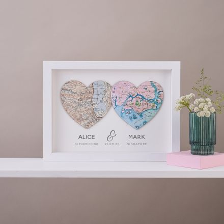 Two map hearts in white wood frame with couples names and date printed beneath.