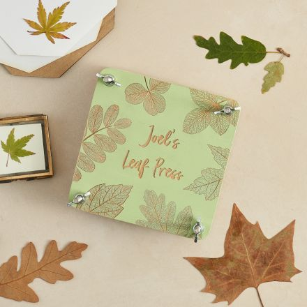 Wooden leaf press painted green with pretty leaf design and 'Joe's leaf press' engraved on the top.