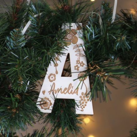 Engraved wooden letter keepsake decoration. Letter A, strung with cream ribbon and hanging on Christmas wreath with Amelia engraved on the front.