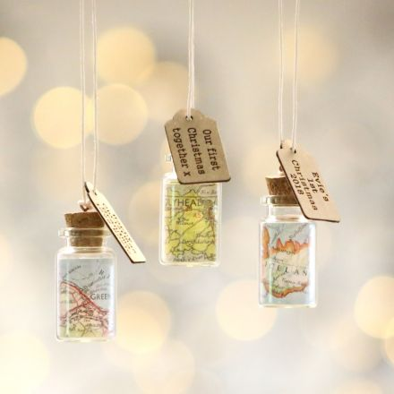 Hanging Christmas decoration. Miniature glass bottle with map inside and strung with twine. Engraved wooden message tag hanging from twine.