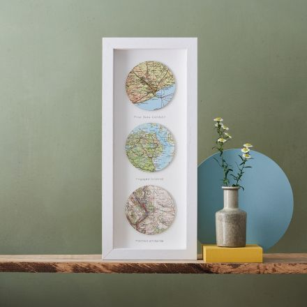 Three map circles framed in a white wood box frame, portrait orientation.