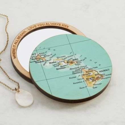Two compact pocket mirrors. One lying face up showing personalised engraving around mirror's edge. The other showing map location.