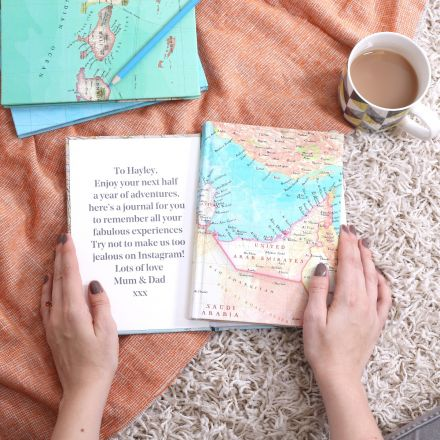 Personalised map location travel journal, four notebooks lying flat one opened to reveal gift message printed inside front cover.