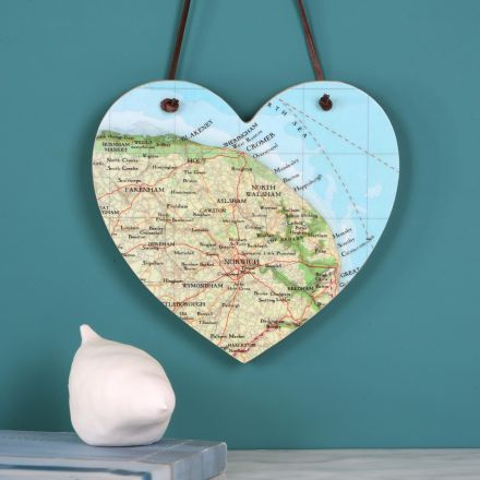 Wooden heart strung with leather cord hanging above mantelpiece. Heart features map of Norwich.