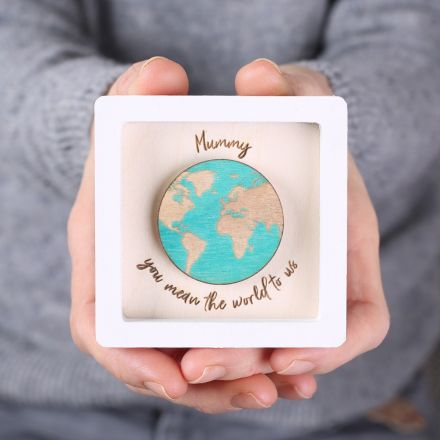 Miniature square black wood frame with tiny gold planet and 'you are my universe' engraved beneath it.