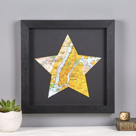 New York map star mounted and framed in black, hung above white mantelpiece.