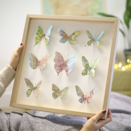 Nine map butterflies in a large light wood box frame.
