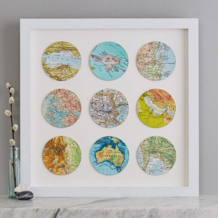 Nine personalised map locations circles framed in white wood box frame and sat on marble mantelpiece