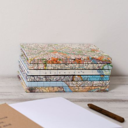 Stack of six map location travel journal notebooks.