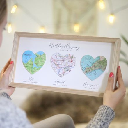 Three map hearts in light wood frame, landscape orientation.  Printed personalisation beneath each heart.