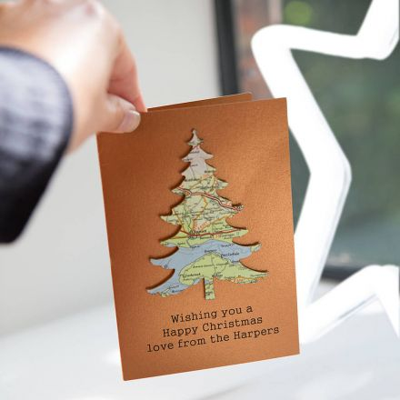 Copper coloured card featuring a map Christmas tree with 'Wishing you a happy Christmas Love from the Harpers' printed beneath.