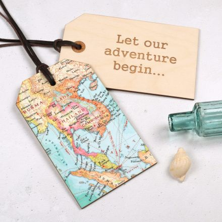Two map luggage tags, one showing map side, one showing reverse with 'Let our adventure begin...' engraved on it. Both strung with leather cord.