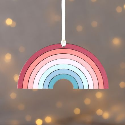 Hanging keepsake decoration. Solid wood rainbow in muted pastel colours strung with cream ribbon.