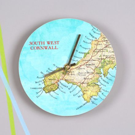 Round wall clock featuring map of Cornwall, hung on grey wall with gold hands.