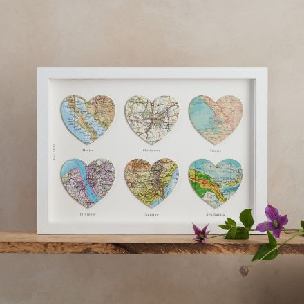 Six map hearts in a white box frame with messages printed beneath each heart