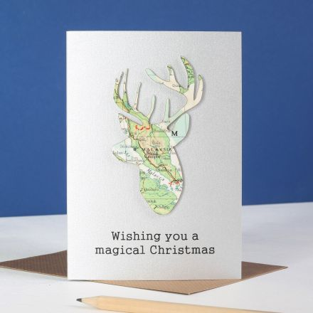 Map stag's head silhouette mounted on silver card with 'wishing you a magical Christmas' printed below.