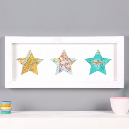 Three map stars in white wood frame, mounted above mantelpiece.