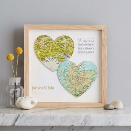 Two map hearts in light wood frame with added printed personalisation. Top right hand corner showing printed 'how we met' text and bottom left corner showing couples names and Est. date.