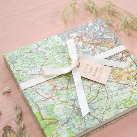 Personalised map location wedding guest book strung with cream ribbon and engraved wooden message tag.