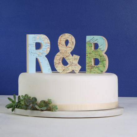 Wooden map letters 'R & B' on top of white wedding cake.