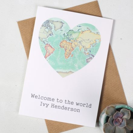 Card featuring a world map in a heart shape with 'Welcome to the world' printed beneath it.