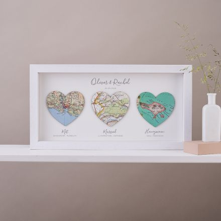 Three map hearts in white wood frame, landscape orientation.  Printed personalisation beneath each heart.