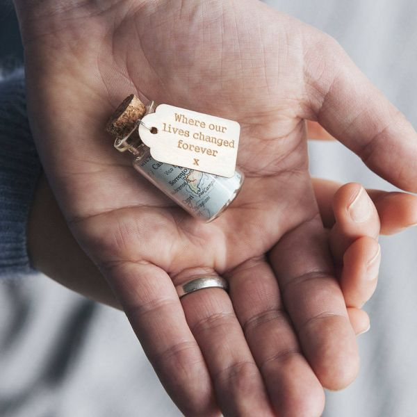 Miniature glass bottle with map inside and wooden gift tag reading 'Where our lives changed forever'.