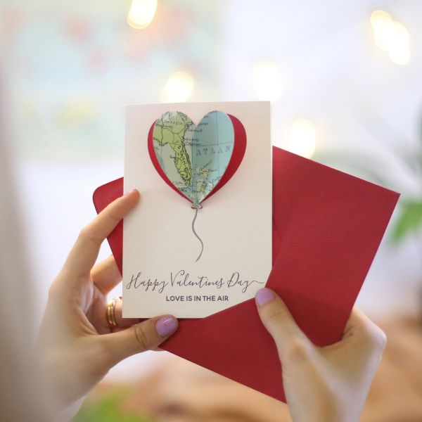 Valentine's card with map balloon in the shape of a heart with 'Happy Valentine's day - love is in the air' printed beneath. Card held against red envelope.