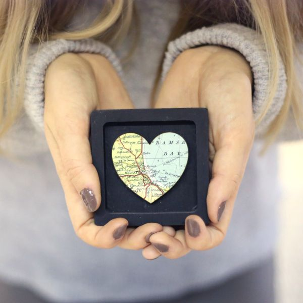 Map heart in a tiny black frame held in palms