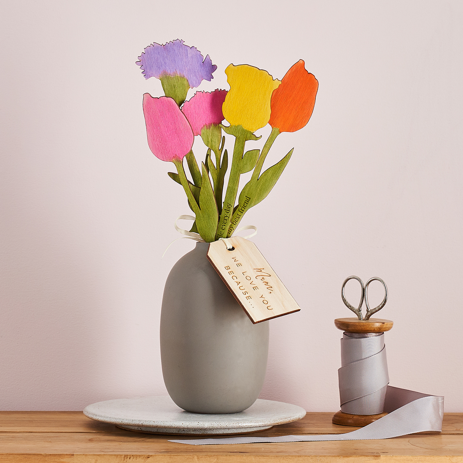 Colourful wooden flowers in a grey vase