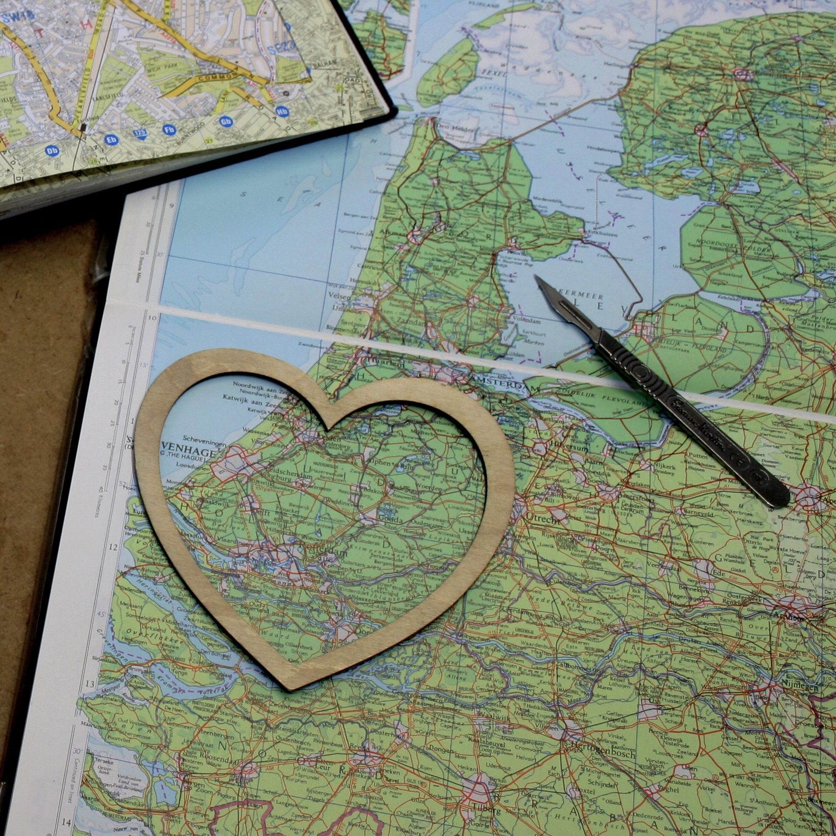Heart stencil on a green map with scalpel.