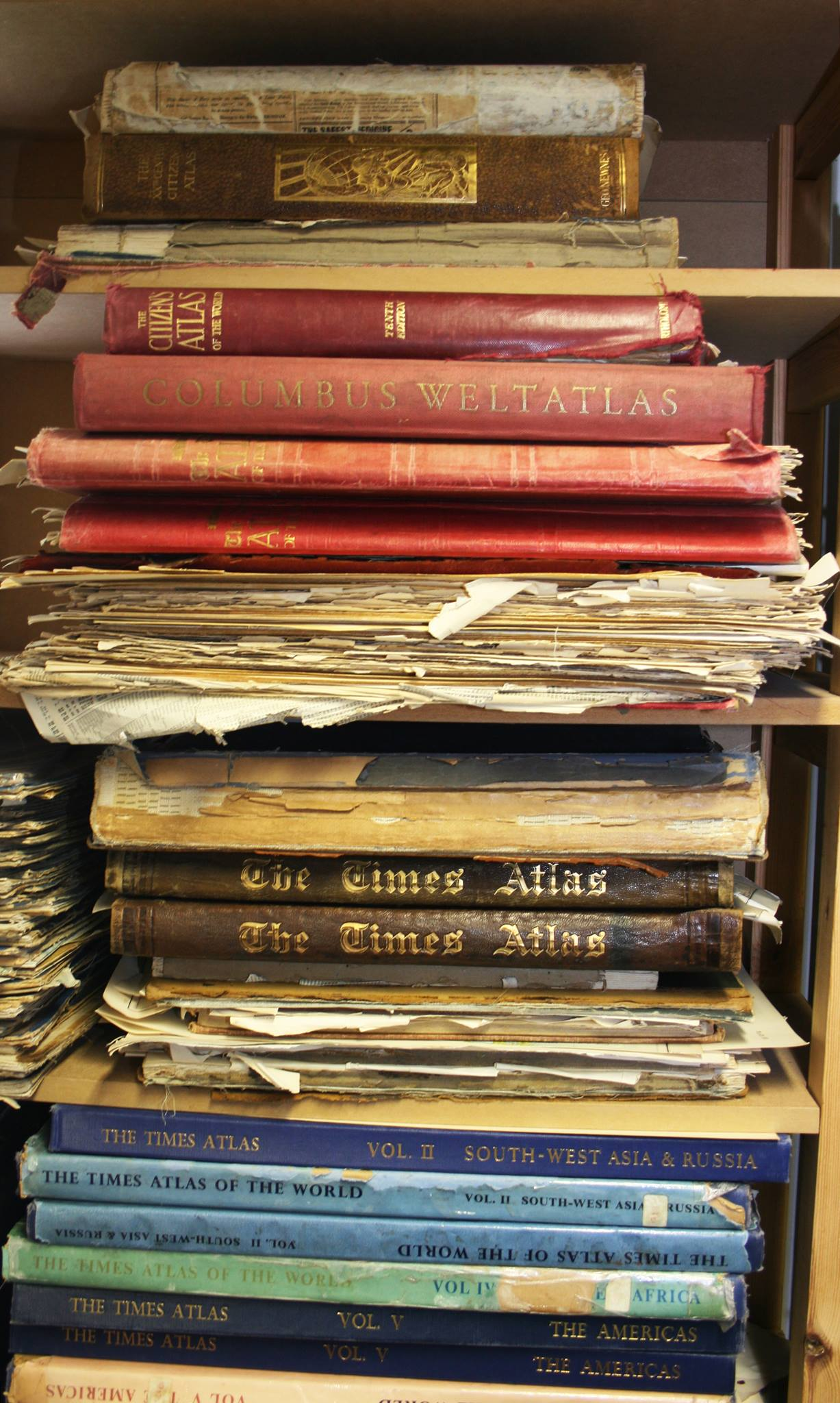 Pile of old antique atlases.